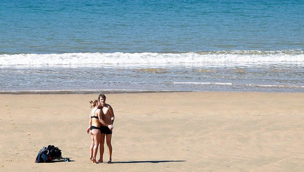 Una pareja disfruta del sol en la playa de La Concha de San Sebastián