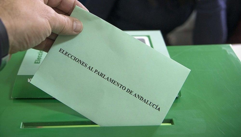 Un votante introduce su papeleta en la urna en un colegio electoral de Jaén
