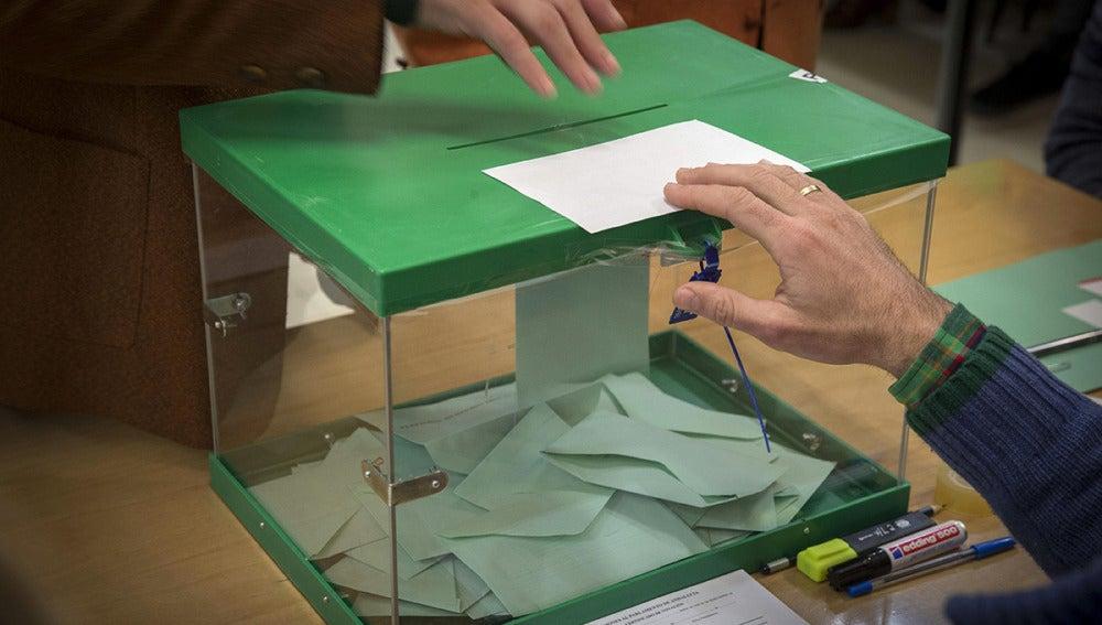 Un votante ejerce su derecho introduciendo la papeleta en la urna en un colegio electoral en Sevilla