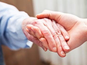 Manos entrelazadas de una anciana y una joven (Archivo)