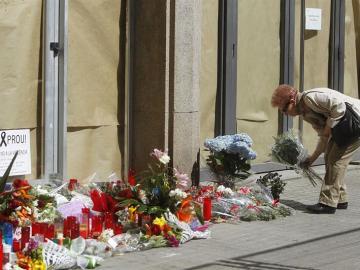 Una mujer deposita flores en el instituto Joan Fuster.