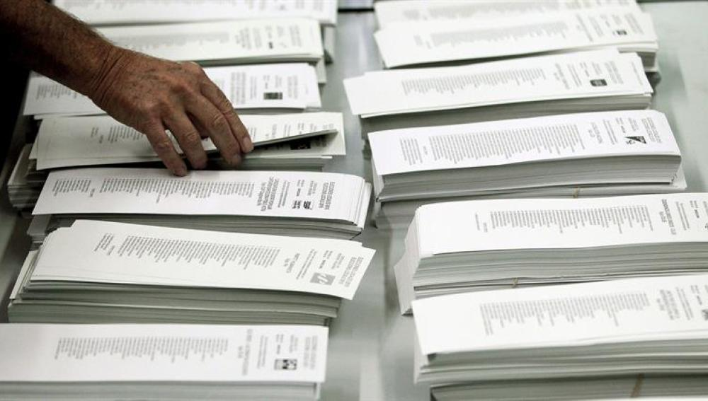 Un ciudadano coge una papeleta de una cabina en un colegio electoral
