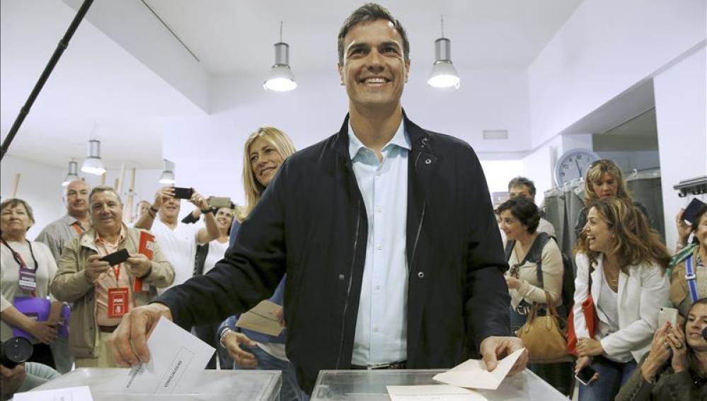 Pedro Sánchez, acompañado de su esposa,detrás, vota en el Centro Cultural Volturno, en Pozuelo de Alarcón
