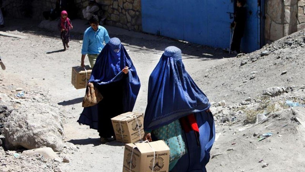 Dos mujeres caminan con cajas en la mano