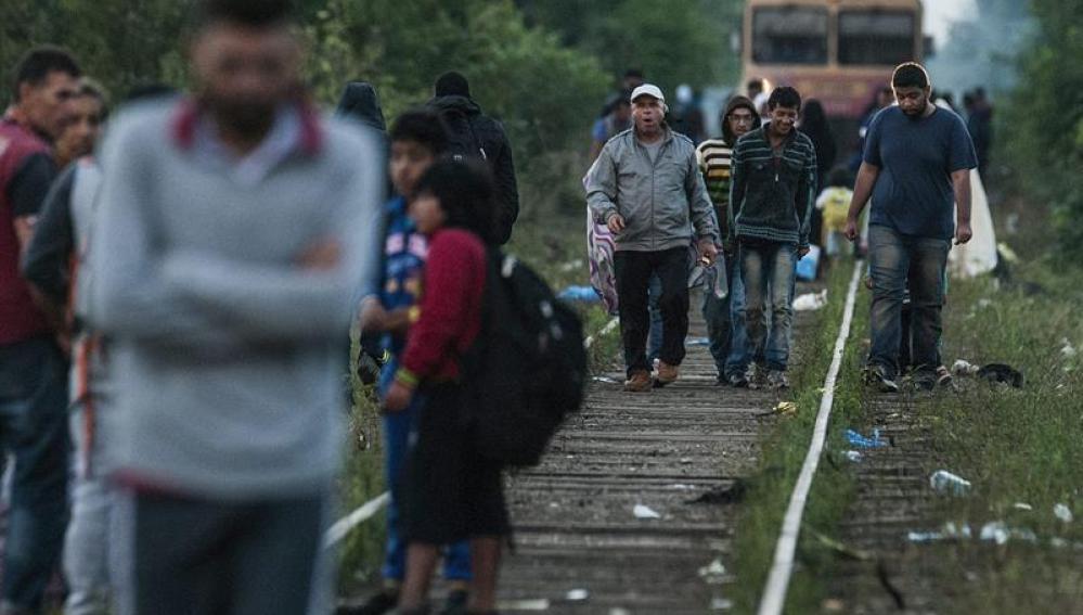 Inmigrantes caminan sobre las vías de un tren en la frontera entre Hungría y Serbia