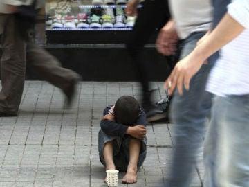 Un niño pide limosna en una calle