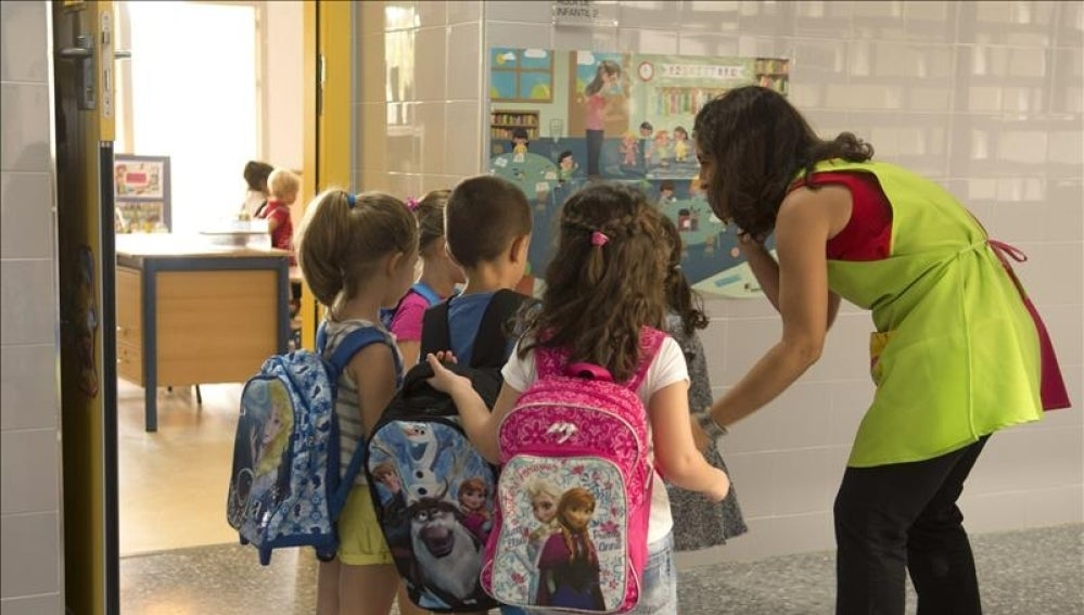 Varios niños entran al colegio con su profesora