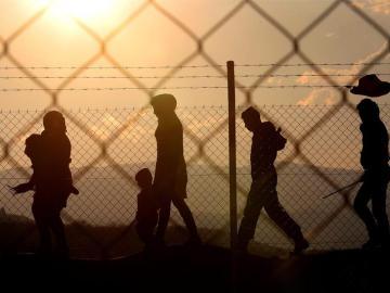 Varios inmigrantes caminan alrededor de una valla