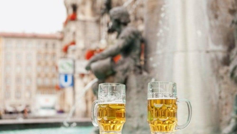 Dos jarras de cerveza frente a una fuente