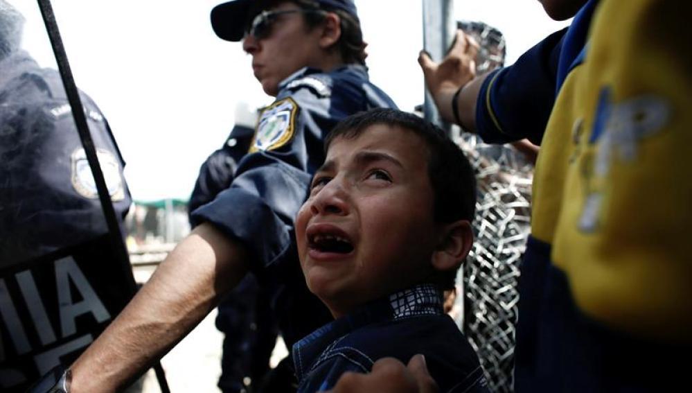 Un niño refugiado llora junto a un Policía