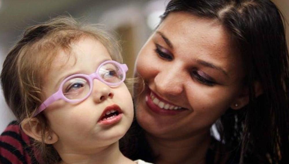 La niña junto a su madre, después de haber sido operada