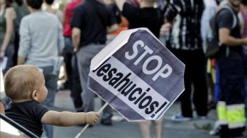 Un niño sostiene un cartel de Stop desahucios