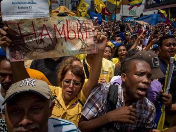 """Una manifestante sostiene un letrero con la palabra """"Hambre"""" en una protesta contra el Gobierno venezolano"""