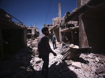 Varias personas caminan sobre los escombros de los edificios destruidos durante unos bombardeos