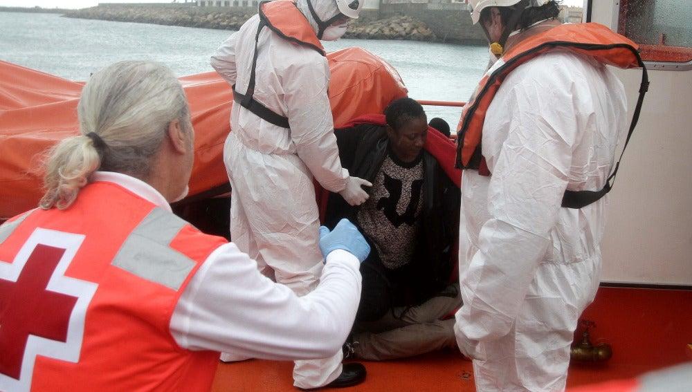 Personal de Cruz Roja ayudan a levantarse a unos inmigrantes que viajaban en una patera y que fueron rescatados por Salvamento Marítimo