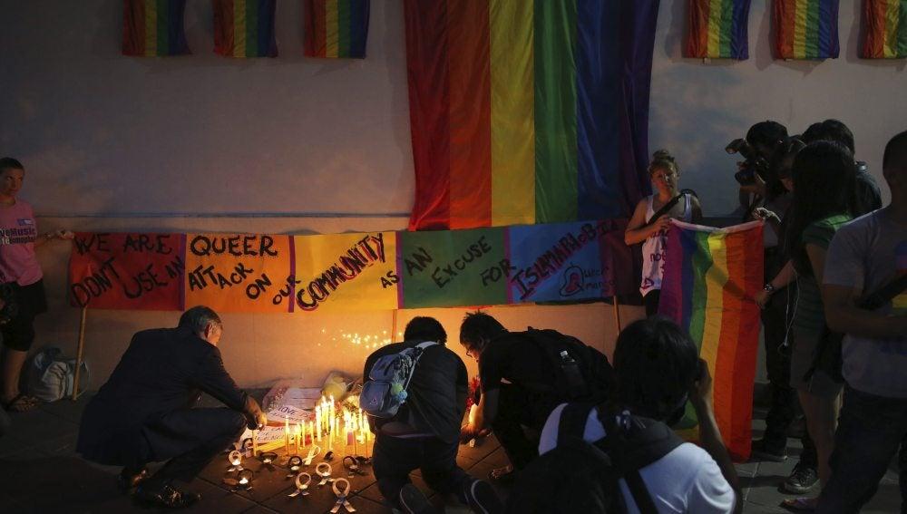 Varias personas encienden una vela en memoria de las victimas del ataque
