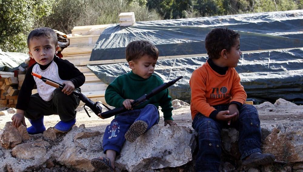 Niños sirios sostienen armas de juguete en un campo de refugiados