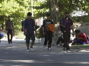 Varios migrantes, de camino a Hungría, marchan por una carretera próxima a Belgrado (Serbia)