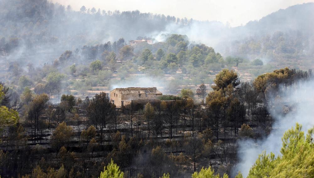 Una masía con el entorno quemado a causa del incendio en La Pobla de Montornès, Tarragona.