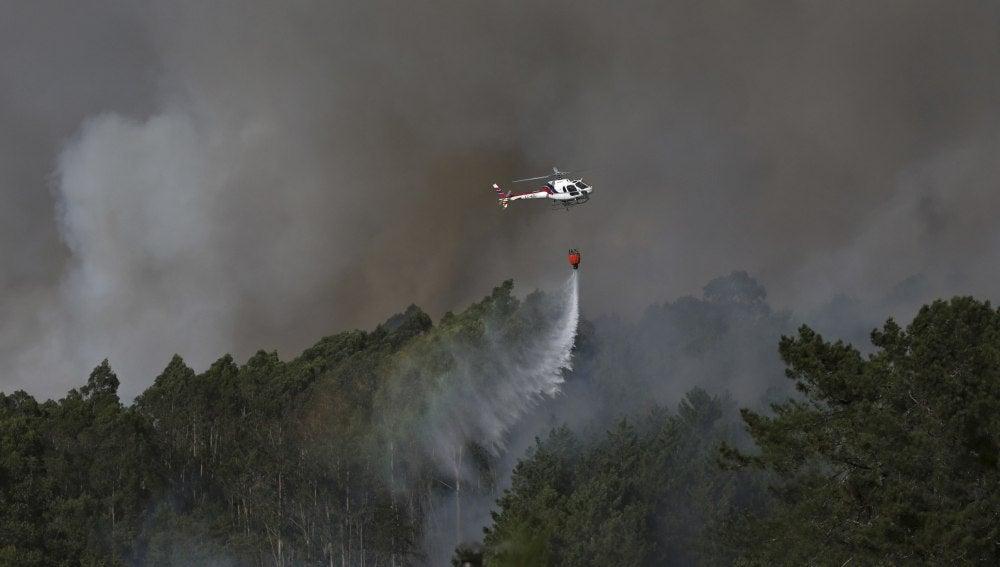 Un helicóptero trabaja en las labores de extinción del incendio originado esta tarde en la parroquia de Tenorio, en Cotobade (Pontevedra)