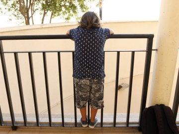 Un niño mira por un balcón