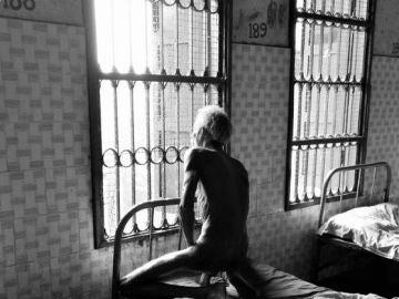 Un hombre, desnudo en un hospital para enfermos mentales de Calcuta, India