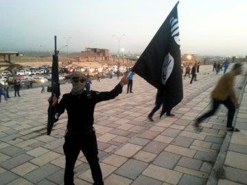 Un combatiente de Daesh sostiene una bandera y un arma en una calle de Mosul