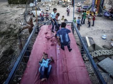 Varios niños juegan en un trampolín en Siria