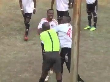 Un árbitro y un jugador pegándose en Zimbabue.