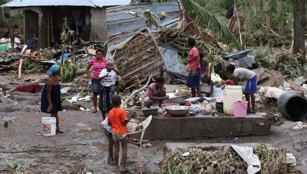 Varias personas intentan recuperar objetos tras el paso del huracán Matthew en Haití