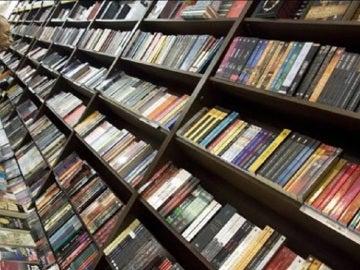 Un hombre ojea varios libros en una librería