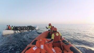 Miembros de ProActiva intentan ayudar a una lancha llena de refugiados