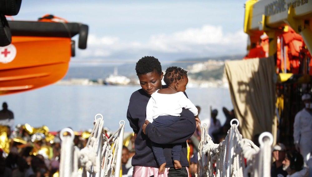 Una mujer sujeta a un bebé tras ser rescatados ambos