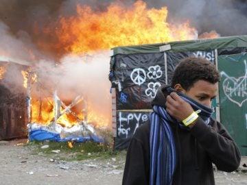 Un migrante se protege el rostro al pasar junto a chabolas en llamas durante el desmantelamiento del campamento conocido como la 'Jungla' de Calais