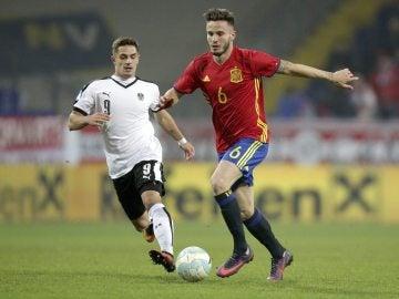 Saúl conduce el balón durante el partido