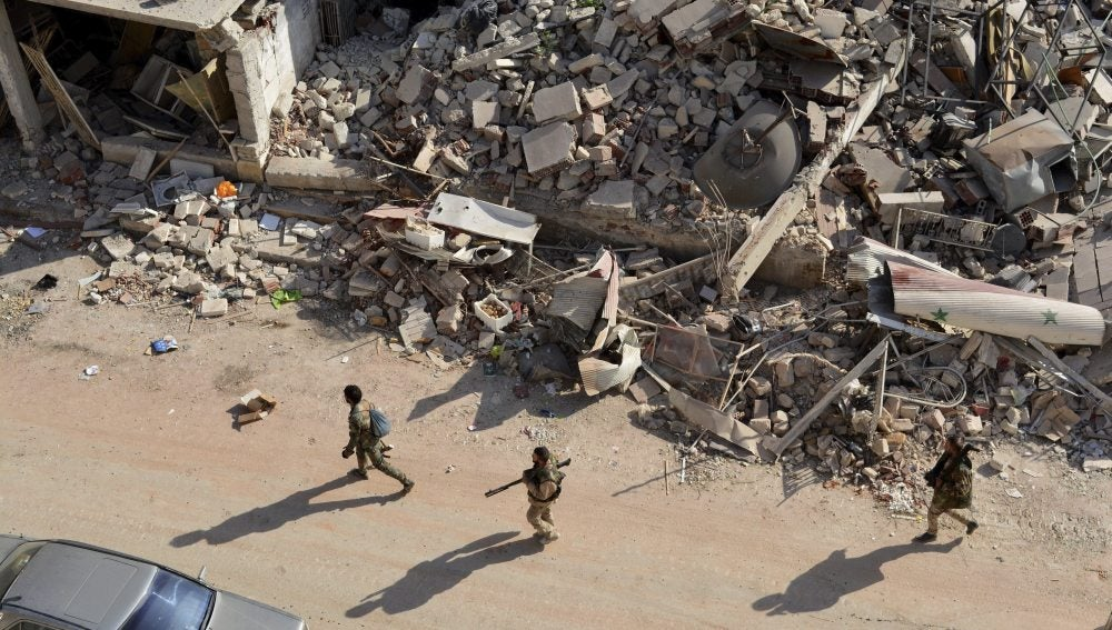 Soldados sirios caminan entre los escombros en el oeste de Alepo