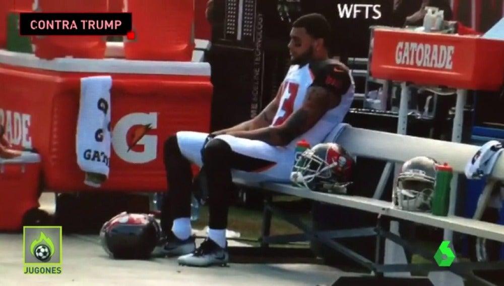 Frame 49.285712 de: Un jugador de la NFL permanece sentado mientras suena el himno de EEUU para protestar contra Trump