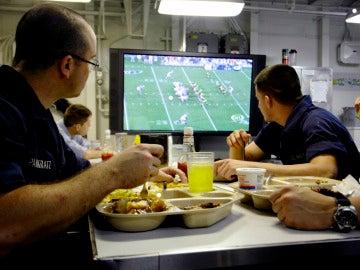 Una familia ve la televisión mientras come