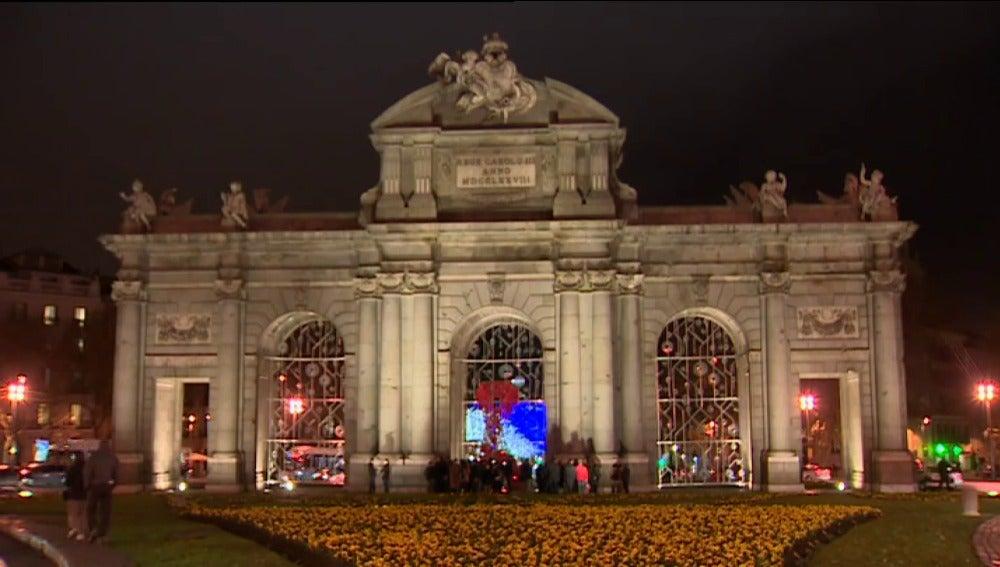 Un lazo rojo adorna la Puerta de Alcalá con motivo del Día Mundial de la lucha contra el VIH