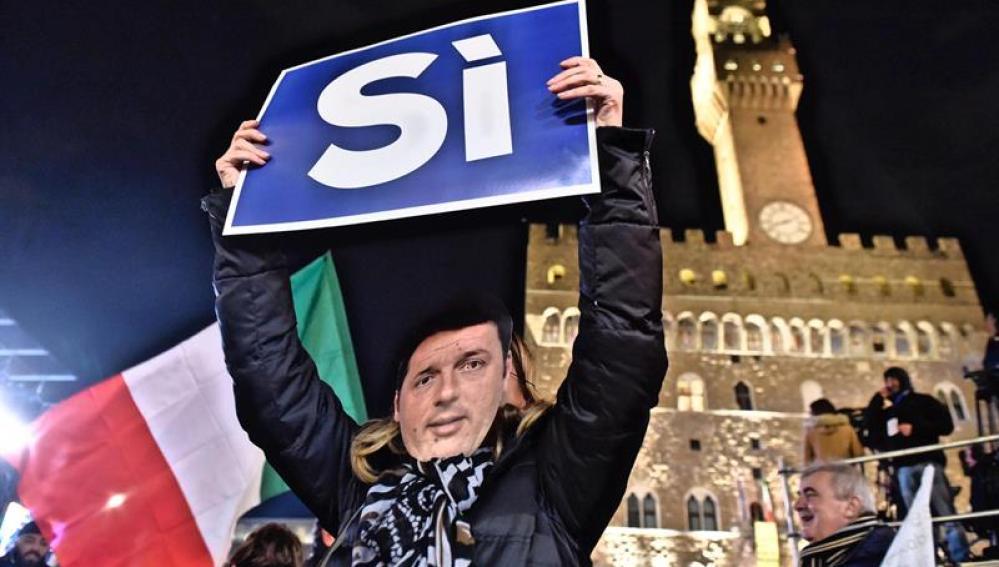 Una mujer lleva una máscara con el rostro del primer ministro italiano Matteo Renzi y sostiene una pancarta en las que se puede leer 'Sí'