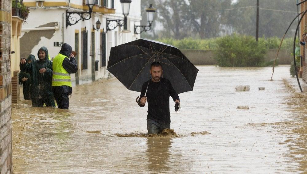 Una persona camina entre las casas inundadas en la barriada Doña Ana de la localidad malagueña de Cártama por las fuertes lluvias caídas esta noche