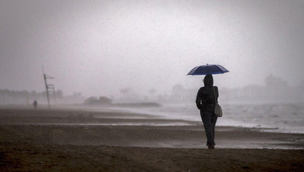 Una persona pasea por la playa de la Malvarrosa bajo la lluvia