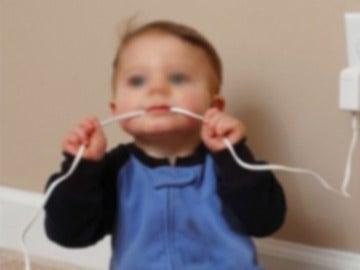 Un bebé muerde un cable (Archivo)