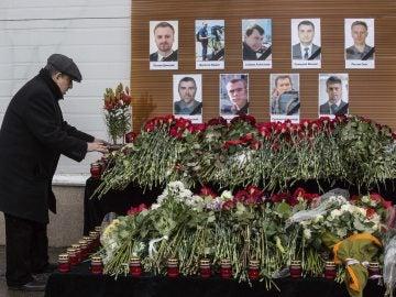 Un hombre deja flores ante los retratos de los periodistas rusos muertos en el accidente de avión