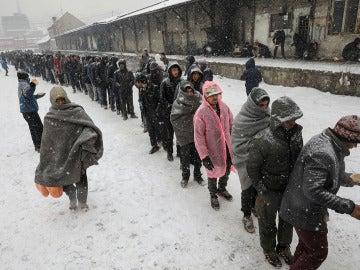 Los refugiados guardan colas por un plato de comida caliente