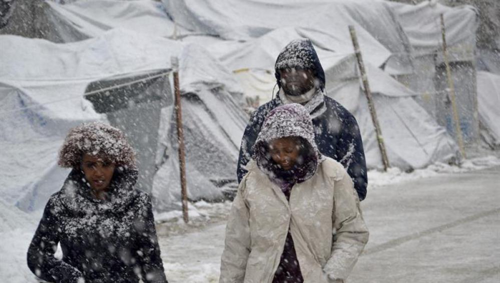 Varios refugiados caminan bajo la nieve en el campamento de refugiados de Moria