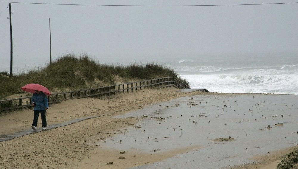 Una señora pasea en las inmediaciones de la playa de Doniños en Ferrol