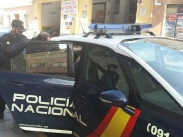 El detenido es introducido en el coche policial.