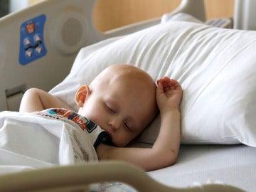 Un menor con el pelo rapado en una cama de hospital
