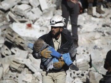 Un casco blanco sirio rescatando a un menor sepultado bajo los escombros